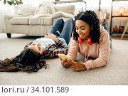 Купить «Women listening to music lying on floor at home», фото № 34101589, снято 20 июня 2020 г. (c) Tryapitsyn Sergiy / Фотобанк Лори