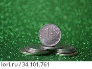 Купить «Российский рубль на стопке монет крупным планом, зелёный блестящий фон», фото № 34101761, снято 24 июня 2020 г. (c) александр афанасьев / Фотобанк Лори