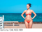 Купить «Beautiful young girl in a striped orange swimsuit sits with her back to us on the bench over backdrop of the blue sea with a small stripe the sky. there is Free space for your text.», фото № 34103189, снято 3 июля 2020 г. (c) age Fotostock / Фотобанк Лори