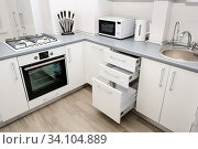 Modern white and black kitchen, electric oven and gas stove, minimalistic clean design. Стоковое фото, фотограф Zoonar.com/Serghei Starus / easy Fotostock / Фотобанк Лори