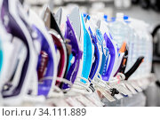 Row of colored electric irons at retail store shelf, selective focus. Стоковое фото, фотограф Zoonar.com/Serghei Starus / easy Fotostock / Фотобанк Лори