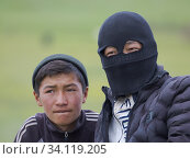 Купить «Young shepherds on their summer pasture. the face mask is protecting the faces from cold, sun and dust. Alaj Valley in front of the Trans-Alay mountain...», фото № 34119205, снято 6 июля 2019 г. (c) age Fotostock / Фотобанк Лори