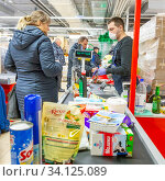 Russia Samara, March 2020: Payment for goods at the checkout in a supermarket. Text in Russian: Provence milk. Редакционное фото, фотограф Акиньшин Владимир / Фотобанк Лори