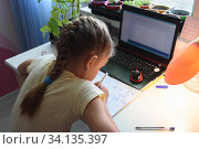 Girl solves math examples in notebook in front of laptop. Стоковое фото, фотограф Иванов Алексей / Фотобанк Лори