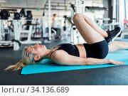 Junge Frau macht ein Workout für die Beine im Liegen im Fitnesscenter. Стоковое фото, фотограф Zoonar.com/Robert Kneschke / age Fotostock / Фотобанк Лори