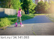 A little girl rides on pink roller skates on asphalt in the summer. The child learns to ride roller skates. Skating. Стоковое фото, фотограф Екатерина Кузнецова / Фотобанк Лори
