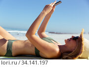 Купить «Woman using smartphone while laying on the beach», фото № 34141197, снято 25 февраля 2020 г. (c) Wavebreak Media / Фотобанк Лори