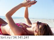Woman using smartphone while laying on the beach. Стоковое фото, агентство Wavebreak Media / Фотобанк Лори
