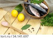Fresh fish mullet in a basket and lemons on wooden table close-up. Стоковое фото, фотограф Татьяна Ляпи / Фотобанк Лори