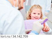 Kind bekommt Zahnpflege Tipps von Kinderzahnarzt für Zahngesundheit und als Prophylaxe. Стоковое фото, фотограф Zoonar.com/Robert Kneschke / age Fotostock / Фотобанк Лори