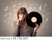 Купить «Young lady holding vinyl record on a brown background with musical notes behind her», фото № 34143081, снято 15 июля 2020 г. (c) easy Fotostock / Фотобанк Лори
