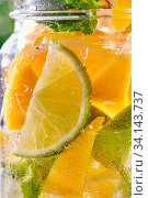 Купить «Glass jar with cold and refreshing detox water with lime, lemon slices and mint with bubbles of air. Close up cooling drink background.», фото № 34143737, снято 14 июля 2020 г. (c) easy Fotostock / Фотобанк Лори