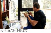 Купить «Man considers paper smartphone and laptop», фото № 34146277, снято 3 июля 2020 г. (c) Ekaterina Demidova / Фотобанк Лори