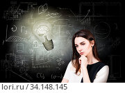 Thoughtful woman looking at bright bulb over icons on chalk board. Стоковое фото, фотограф Zoonar.com/Kotin Dmitrii / age Fotostock / Фотобанк Лори