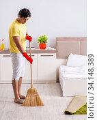 Купить «Young handsome man cleaning in the bedroom», фото № 34148389, снято 28 июня 2018 г. (c) Elnur / Фотобанк Лори