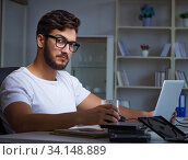 Young man staying late in office to do overtime work. Стоковое фото, фотограф Elnur / Фотобанк Лори