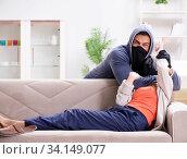 Купить «Armed man assaulting young woman at home», фото № 34149077, снято 15 декабря 2017 г. (c) Elnur / Фотобанк Лори