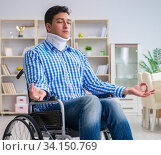 Young man suffering from injury on wheelchair at home. Стоковое фото, фотограф Elnur / Фотобанк Лори