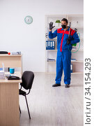Young male contractor disinfecting office. Стоковое фото, фотограф Elnur / Фотобанк Лори