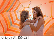 Mom with a small daughter walks along the beach with an umbrella on a sunny summer day. Стоковое фото, фотограф Акиньшин Владимир / Фотобанк Лори
