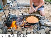 Купить «A young man cooks outdoors pilaf in a cauldron at the stake.», фото № 34155237, снято 19 июля 2019 г. (c) Акиньшин Владимир / Фотобанк Лори