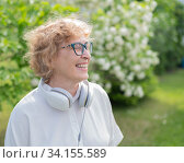 An elderly Caucasian woman walks in a park and listens to music. Smiling pensioner took off her headphones and enjoys the aroma of flowering trees in the garden. Редакционное фото, фотограф Михаил Решетников / Фотобанк Лори