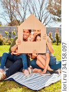 Eltern und zwei Kinder halten ein Modell Haus als Symbol für Eigenheim und Hausbau. Стоковое фото, фотограф Zoonar.com/Robert Kneschke / age Fotostock / Фотобанк Лори