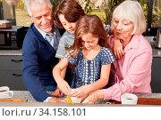Zwei Kinder backen Pizza mit den beiden Großeltern in der Küche. Стоковое фото, фотограф Zoonar.com/Robert Kneschke / age Fotostock / Фотобанк Лори