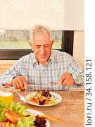 Senior Mann als Vegetarier beim Essen von Salat beim Mittagessen oder Abendessen. Стоковое фото, фотограф Zoonar.com/Robert Kneschke / age Fotostock / Фотобанк Лори