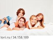 Glückliche Eltern und ihre zwei Kinder morgens zusammen im Bett im Schlafzimmer. Стоковое фото, фотограф Zoonar.com/Robert Kneschke / age Fotostock / Фотобанк Лори
