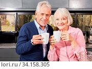 Senioren Paar im Ruhestand in der Küche mit einer Tasse oder einem Becher Kaffee. Стоковое фото, фотограф Zoonar.com/Robert Kneschke / age Fotostock / Фотобанк Лори