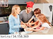 Fröhliche Familie mit zwei Kindern beim Backen und Teig kneten zusammen in der Küche. Стоковое фото, фотограф Zoonar.com/Robert Kneschke / age Fotostock / Фотобанк Лори