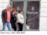 Sofia, Bulgaria - 12 May, 2019: People pass by the office of OneCoin cryptocurrency founded by Ruja Ignatova. Стоковое фото, фотограф Zoonar.com/Cylonphoto / age Fotostock / Фотобанк Лори