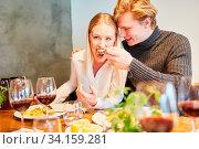 Junges Paar hat Spaß beim Mittagessen oder Abendessen zusammen im Restaurant. Стоковое фото, фотограф Zoonar.com/Robert Kneschke / age Fotostock / Фотобанк Лори