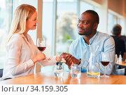 Junge Frau und afrikanischer Freund beim Flirten beim Dating im Restaurant. Стоковое фото, фотограф Zoonar.com/Robert Kneschke / age Fotostock / Фотобанк Лори
