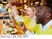 Freunde schauen Spiel einer Mannschaft als Fans im Restaurant oder Pub und jubeln. Стоковое фото, фотограф Zoonar.com/Robert Kneschke / age Fotostock / Фотобанк Лори