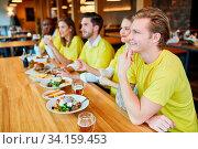 Freunde als Fans in Trikots schauen Spiel einer Mannschaft im Restaurant. Стоковое фото, фотограф Zoonar.com/Robert Kneschke / age Fotostock / Фотобанк Лори