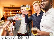 Männer als Freunde und Kumpel beim Bier trinken zusammen im Pub an der Theke. Стоковое фото, фотограф Zoonar.com/Robert Kneschke / age Fotostock / Фотобанк Лори