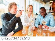 Junger Mann mit Freunden als Gast im Restaurant beim Zuprosten mit Rotwein. Стоковое фото, фотограф Zoonar.com/Robert Kneschke / age Fotostock / Фотобанк Лори