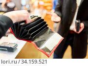 Kellner sucht für Gast in Brieftasche nach Wechselgeld beim Bezahlen mit Bargeld. Стоковое фото, фотограф Zoonar.com/Robert Kneschke / age Fotostock / Фотобанк Лори