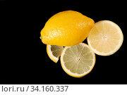 Unterschiedlich aufgeschnittene Zitrone auf schwarzem Hintergrund, links Platz zur Beschriftung. Стоковое фото, фотограф Zoonar.com/Helga Mahler / easy Fotostock / Фотобанк Лори