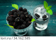 Купить «Fresh blackberry. Juicy blackberry in a bowl and a glass of cold ice water with berries on a wooden table. View from above. Copy space.», фото № 34162585, снято 14 июля 2020 г. (c) easy Fotostock / Фотобанк Лори