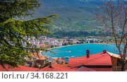Panoramic image of hillside red tiled rooftops of houses on the shore of Lake Ohrid, Northern Macedonia. Стоковое фото, фотограф Zoonar.com/Pawel Opaska / easy Fotostock / Фотобанк Лори