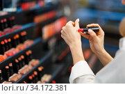 Woman choosing lipstick in cosmetics store. Стоковое фото, фотограф Tryapitsyn Sergiy / Фотобанк Лори