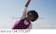 African American woman doing pyoga positon on the beach and blue sky background. Стоковое видео, агентство Wavebreak Media / Фотобанк Лори