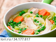 Fresh homemade chicken noodle soup with carrot, peas and celery in green soup bowl (Selective Focus, Focus in the middle of the soup) Стоковое фото, фотограф Zoonar.com/Ildi Papp / easy Fotostock / Фотобанк Лори