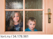 Portrait of a cute little Caucasian boy and girl hiding behind a door with glass windows while playing hide and seek. Стоковое фото, фотограф Zoonar.com/Pawel Opaska / easy Fotostock / Фотобанк Лори