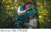Купить «Woman instructor putting on a little girl protective helmet for the rope adventure», видеоролик № 34179633, снято 13 июля 2020 г. (c) Константин Шишкин / Фотобанк Лори