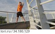 Купить «Sporty Caucasian man training on a bridge», видеоролик № 34180129, снято 30 мая 2019 г. (c) Wavebreak Media / Фотобанк Лори
