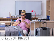 Купить «Young male employee preparing for the trip», фото № 34186761, снято 28 мая 2020 г. (c) Elnur / Фотобанк Лори